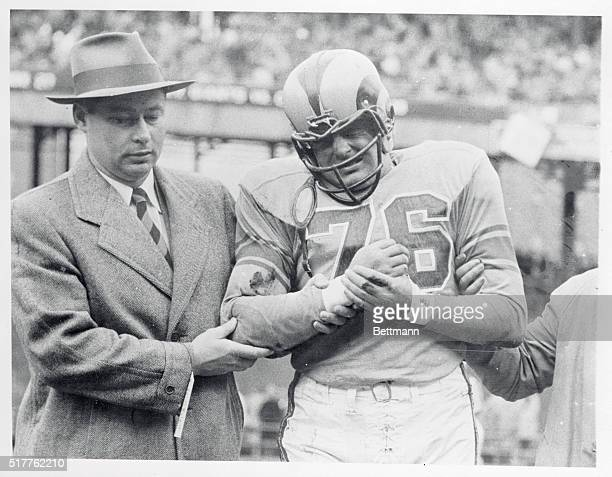 Harland Svare of the Rams is helped off the field by a trainer after injuring his right shoulder during the first period of today's game with the...