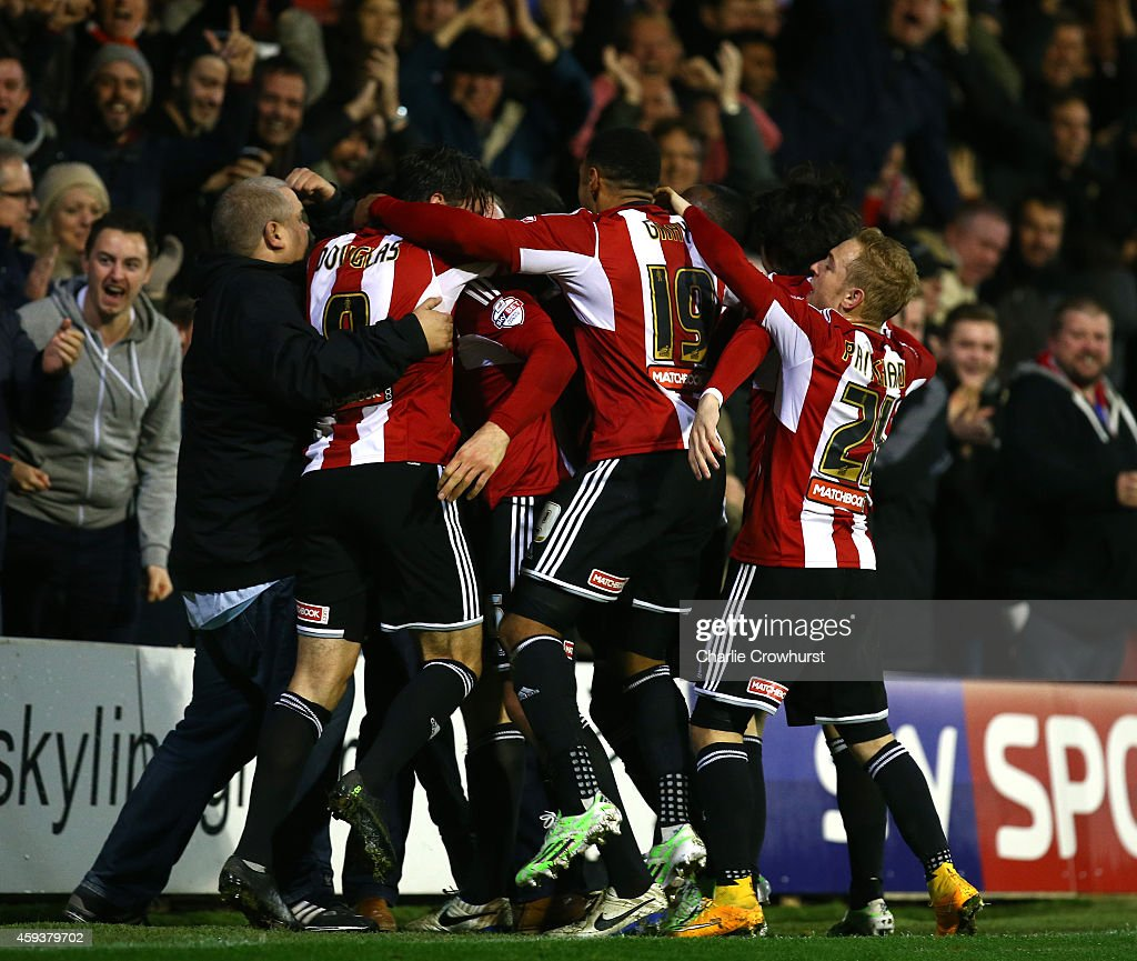 Harlee Dean of Brentford celebrates with team mates after scoring the teams first goal and the equaliser during the Sky Bet Championship match between Brentford and Fulham at Griffin Park on November 21, 2014 in Brentford, England,