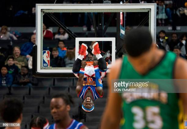 TOPSHOT Harlem Globetrotter's Hot Shot Swanson hangs upside down from the rim after being lifted in the air by teammates for a slam dunk during their...