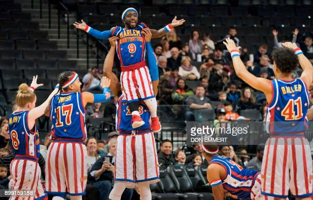 Harlem Globetrotter's Hot Shot Swanson is lifted in the air by 'Beast' Douglas during their game against the Washington Generals at the Barclays...