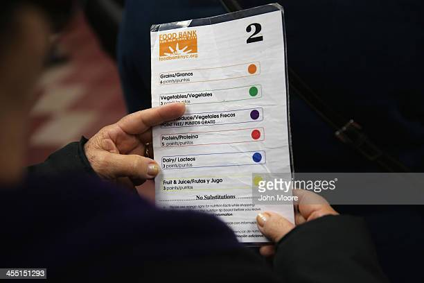 Harlem resident looks at a color coding system before choosing free groceries at the Food Bank For New York City on December 11 2013 in New York City...