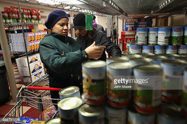 Harlem residents choose free groceries at the Food Bank For New York City on December 11 2013 in New York City The food bank distributes dry canned...