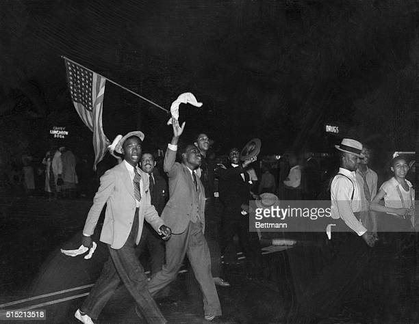 Harlem residents march carrying American flags and placards demanding the ousting of 'Hitler's agents and spies' during an antiNazi parade following...