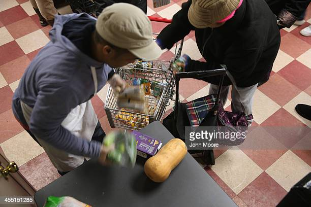 Harlem residents pack free groceries at the Food Bank For New York City on December 11 2013 in New York City The food bank distributes dry canned and...