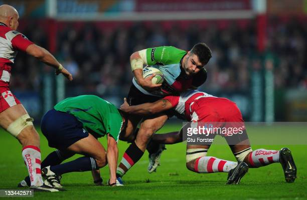 Harlequins forward Nick Easter runs through a tackle from Akapusi Qera and referee Christophe Berdos during the Heineken Cup match between Gloucester...