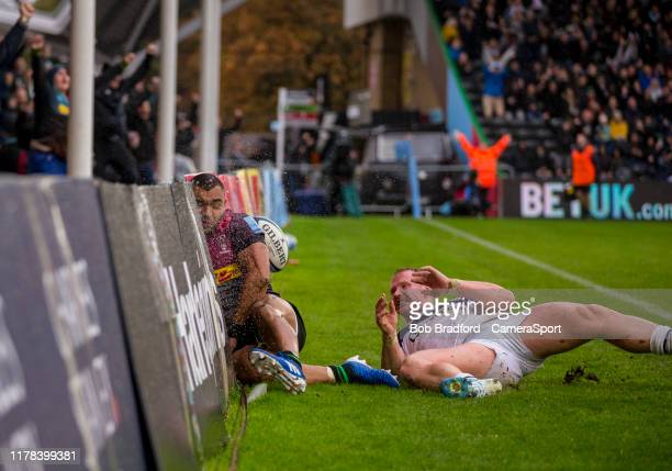 Harlequins' Joe Marchant crash into the advertising boards after scores his sides first try during the Gallagher Premiership Rugby match between...