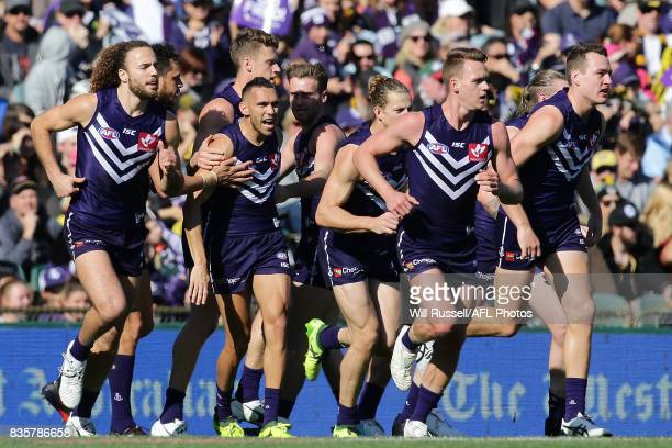 Harley Bennell of the Dockers celebrates with team mates after scoring a goal during the round 22 AFL match between the Fremantle Dockers and the...