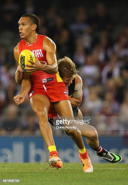 Harley Bennell of the Suns handballs whilst being tackled byJack Newnes of the Saints during the round nine AFL match between the St Kilda Saints and...