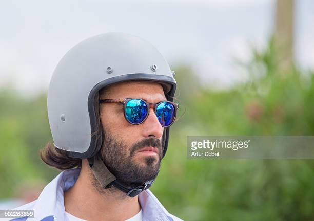 Harley Davidson motorbike rider with prominent beard wearing helmet and sunglasses in a American motorbike meeting in Barcelona