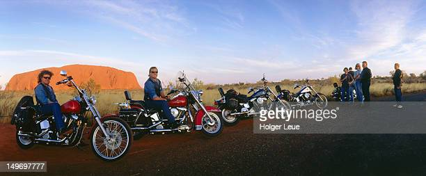 Harley Davidsons and riders at sunset with Uluru in background.