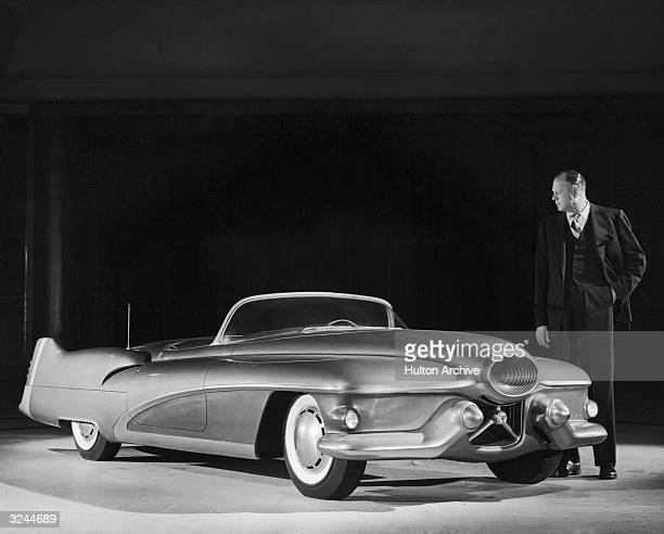 Harley J Earl vice president in charge of styling at General Motors looks over the full scale model of the 1951 Buick Le Sabre sports car The...