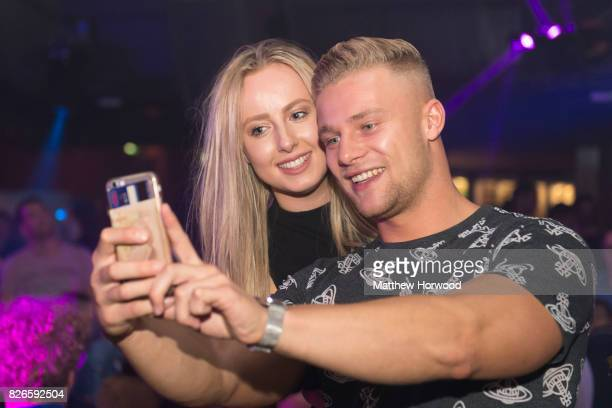 Harley Judge from the ITV reality TV series 'Love Island' takes a selfie with a fan at Walkabout on August 5 2017 in Cardiff Wales