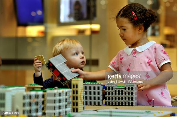 Harli Cook aged 15 months from Ashford in Kent watches as Annalise MooreEast aged 3 from London rearrange a LEGO model of the Olympic Athletes...