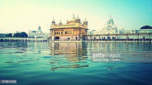 harmandir sahib temple reflection on pond against clear sky - golden temple india stock photos and pictures