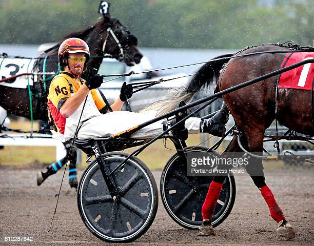 Harness racing driver Nick Graffam of Falmouth gives 'thumbs up' towards his father Michael Graffam and horse owner Daine Frazier of Kennebunk after...