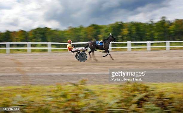 Harness racing driver Nick Graffam of Falmouth steers Pembroke Boogie around the track at Oxford County Fair before a catchdrive in the 10th race