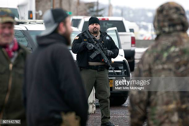 Harney County Sheriff stands guard at Harney County Courthouse while protesters gathered to voice their opposition against law enforcement actions...