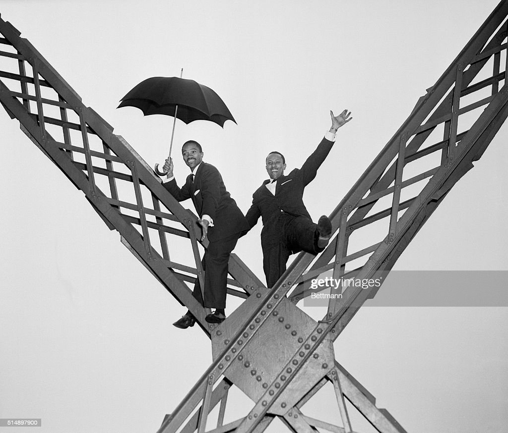 Harold (left) and Fayard Nicholas do some high steps in a high place, the Eiffel Tower to be exact, as they get around to see the sights in Paris. The two Americans, nightclub entertainers, are currently at the Paris Music Hall. Harold seems to think an umbrella is a good idea when stepping around at the Eiffel Tower.