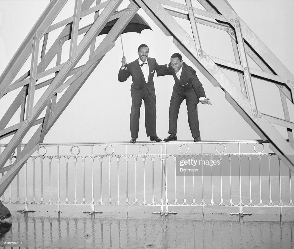 Harold (left) and Fayard Nicholas so dome high steps in a high place, the Eiffel Tower to be exact, as they get around to see the sights in Paris. The two Americans, nightclub entertainers, are currently at the Paris Music Hall. Harold seems to think an umbrella is a good idea when stepping around at the Eiffel Tower.