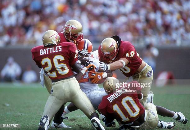 Harold Battles, Derrick Brooks, Todd Rebol and Richard Coes of the Florida State Seminoles tackle an unidentified player from the Clemson Tigers on...