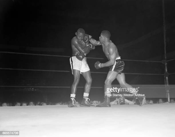 Harold Carter delivers a left to the jaw of Young Jack Johnson during their bout at Madison Square Garden in New York New York November 16 1956