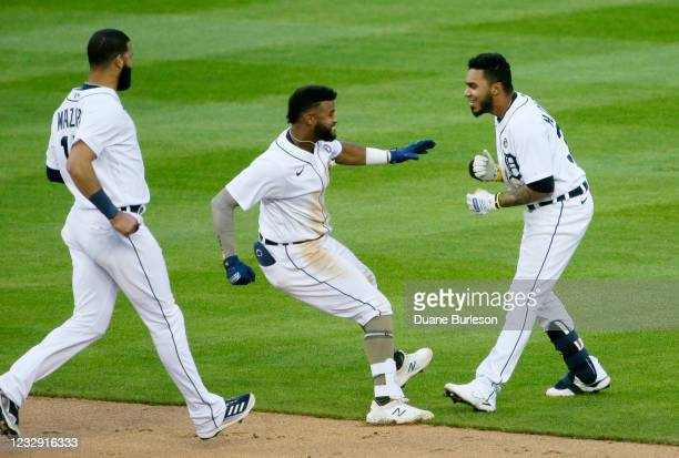 Harold Castro of the Detroit Tigers celebrates with Willi Castro and Nomar Mazara after hitting a walk-off single to defeat the Chicago Cubs 9-8 in...