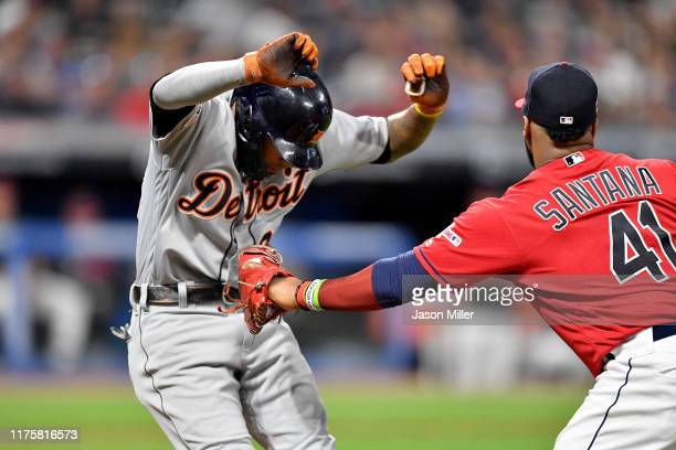 Harold Castro of the Detroit Tigers is tagged out by first baseman Carlos Santana of the Cleveland Indians during the fifth inning tries to dodge at...