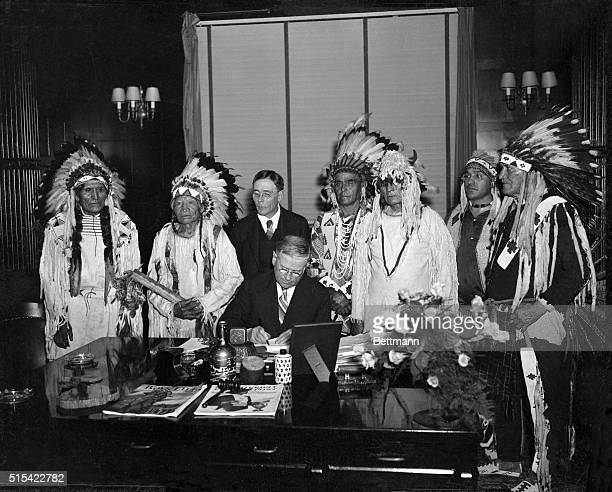 Harold Ickes, Secretary of the Interior, signs the Flathead Indian Constitution as John Collier, Commissioner of Indian Affairs, Chief Carlo, and...