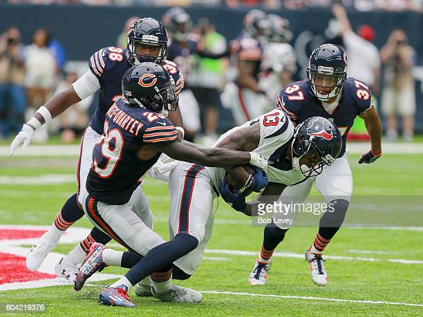 Harold JonesQuartey of the Chicago Bears attempts to strip the ball away from Braxton Miller of the Houston Texans as Bryce Callahan and Adrian Amos...