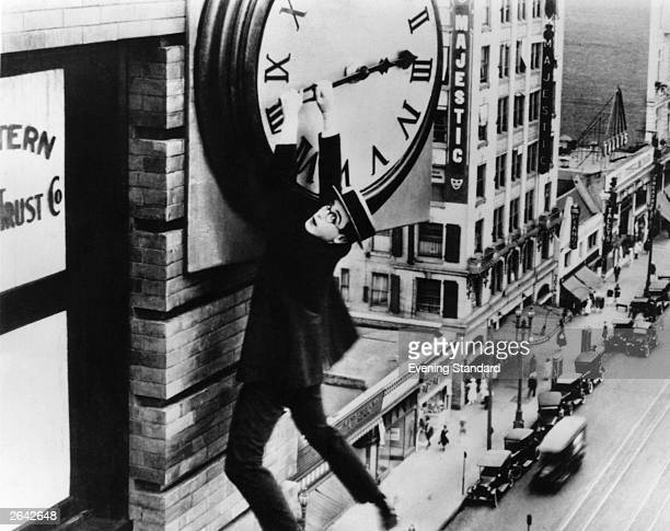 Harold Lloyd finds himself in a precarious situation dangling from a clock in a scene from the film 'Safety Last'