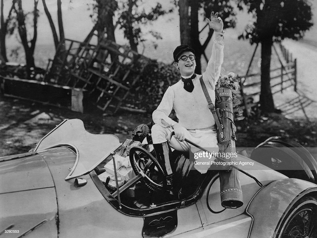 Harold Lloyd (1893-1971) gives a wave from his car in the silent comedy 'Girl Shy'.