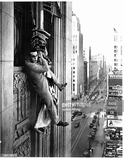 Harold Lloyd hangs from a flag in a scene from the film 'Feet First' 1930