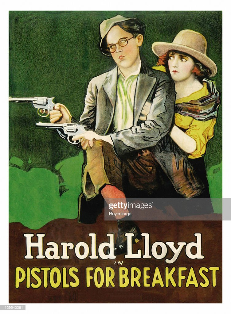 Harold Lloyd holds two guns in front a young girl on a poster that advertises the movie 'Pistols for Breakfast,' 1919.