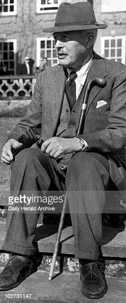 Harold Macmillan, British politician, April 1956. MacMillan, with pipe and walking stick, relaxes at Birch Grove, Sussex where he was staying with...