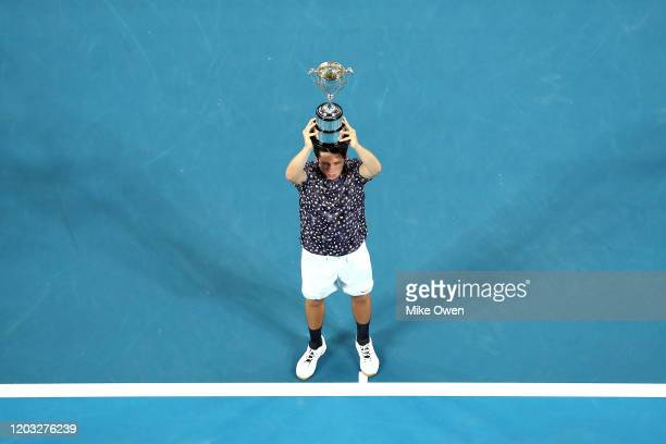 Harold Mayot of France lifts the Championship trophy after winning his Junior Boys' Singles Final against Arthur Cazaux of France on day thirteen of...