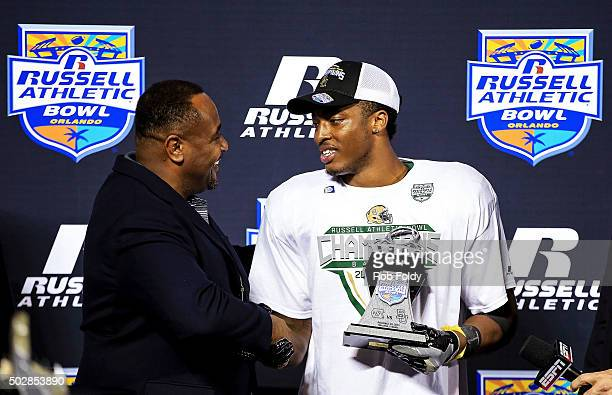 Harold Mills president of Florida Citrus Sports hands the MVP trophy to Johnny Jefferson of the Baylor Bears after the Russell Athletic Bowl game...