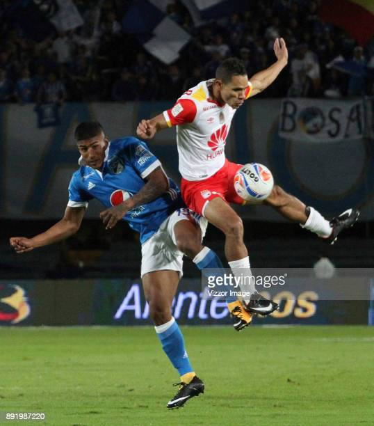Harold Mosquera Millonarios goes for a header with Anderson Plata of Independiente Santa Fe during the first leg match between Millonarios and Santa...