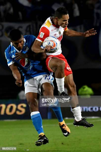 Harold Mosquera of Millonarios vies for the ball with Anderson Plata of Independiente Santa Fe during the first leg match between Millonarios and...
