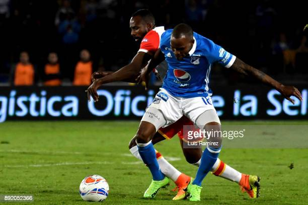 Harold Mosquera of Millonarios vies for the ball with Juan David Valencia of Independiente Santa Fe during the first leg match between Millonarios...