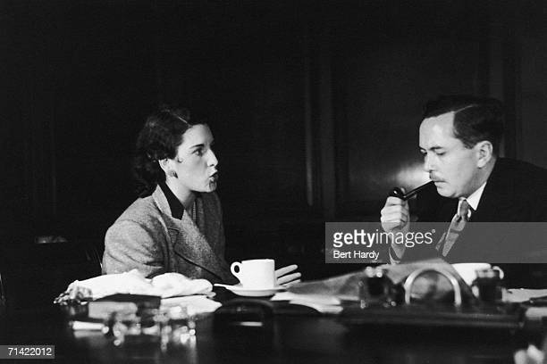 Harold Wilson President of the Board of Trade listens as Mrs Lilian Chandler a housewife and mother of two from Bexleyheath questions him about the...