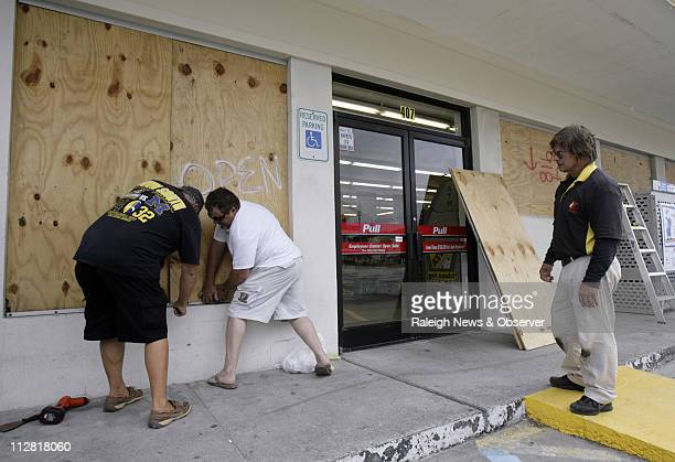 Harold Wright left Roy Renegar center and Chris Kroll board up the windows at the Kangaroo Mart as Hurricane Earl approaches Atlantic Beach North...