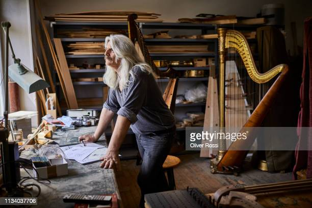 harp maker working on plans in his workshop - manufacturing stock pictures, royalty-free photos & images