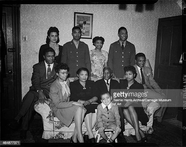 Harper family with Frank Bryant seated in center Nate Harper Alice Harper Lucinda and Charles Harper Sr Doris Harper and Walt Harper seated on sofa...