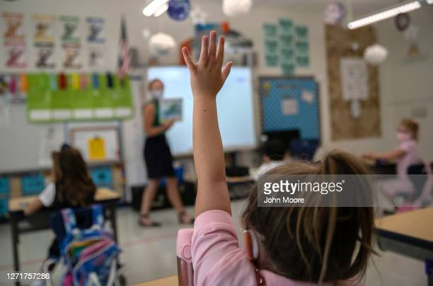 Harper Shea , raises her hand during her first day of kindergarten on September 9, 2020 in Stamford, Connecticut. For millions of kindergartners...