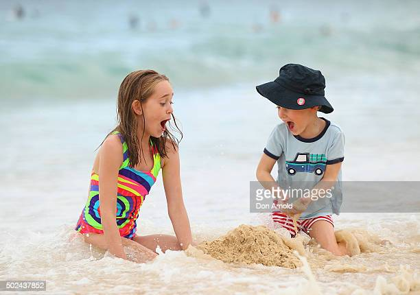 Harper Smith and Truman Smith react as their well constructed sand castle is run over by a wave at Bondi Beach on December 25 2015 in Sydney...