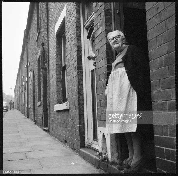 Harper Street, Middleport, Burslem, Stoke-on-Trent, 1965-1968. An elderly woman standing in the doorway of a terraced house on the south side of...