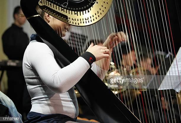 Harpist jugando en concert.orchestra en la parte posterior