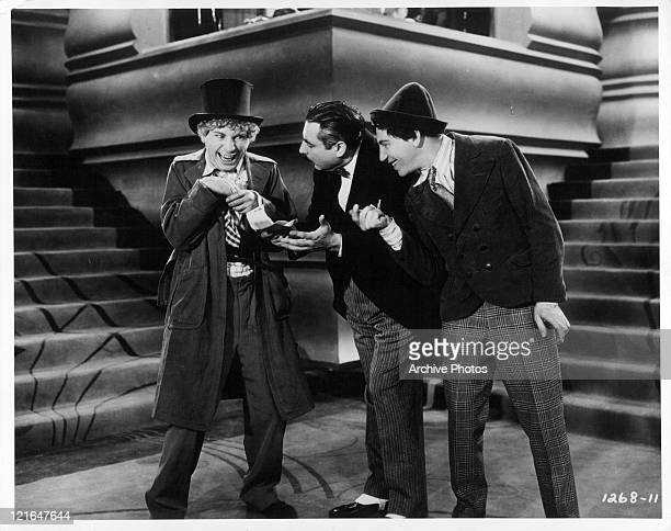 Harpo Marx in a top hat with Zeppo and Groucho Marx looking at him in a scene from the film 'Animal Crackers' 1930