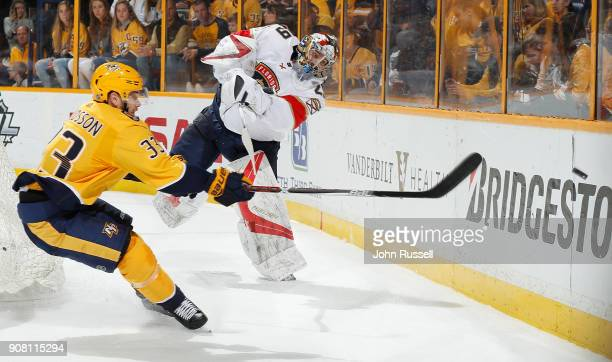 Harri Sateri of the Florida Panthers clears the puck behind the net against Viktor Arvidsson of the Nashville Predators during an NHL game at...