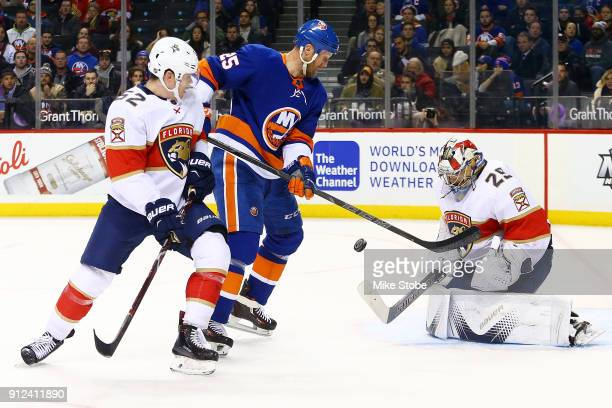 Harri Sateri of the Florida Panthers makes a save against Jason Chimera of the New York Islanders with teammate MacKenzie Weegar defending during the...